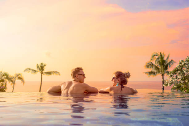 Happy couple on honeymoon in luxury hotel pool Happy couple enjoying honeymoon in luxury hotel pool infinity pool stock pictures, royalty-free photos & images