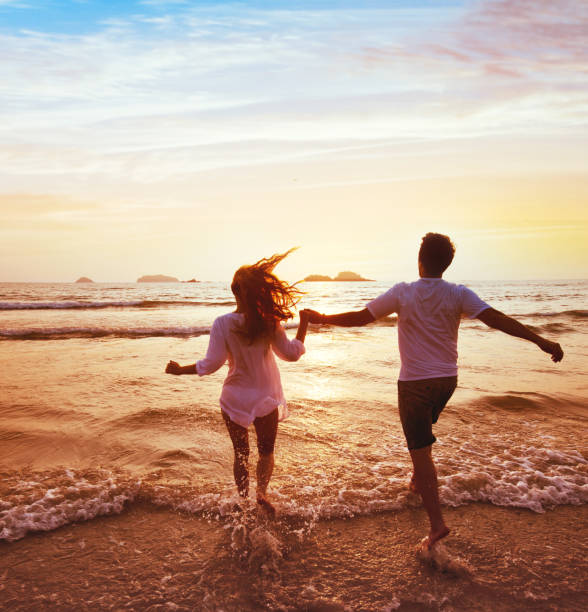 happy couple on honeymoon vacation travel, beach holidays happy couple on honeymoon vacation travel, romantic dream beach holidays, happiness background, silhouettes of man and woman running to the sea at sunset together honeymoon stock pictures, royalty-free photos & images