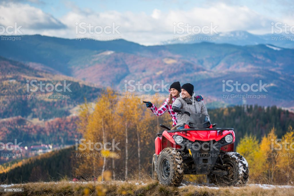Happy couple on red quad bike riding in the mountains. Young man driving the ATV, girlfriend pointing at something interesting. Beautiful landscape of mountains and forest at autumn day stock photo