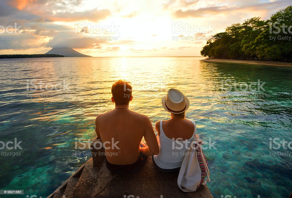 Happy couple on the pier on background colorful sunset