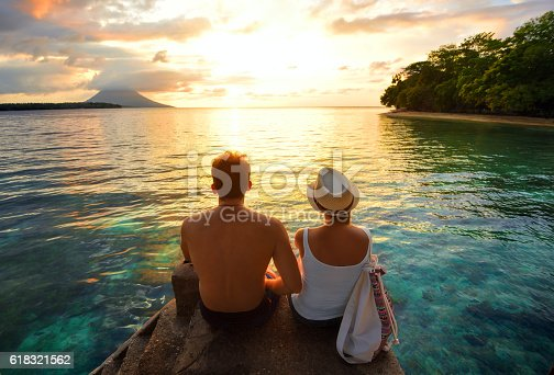 istock Happy couple on the pier on background colorful sunset 618321562