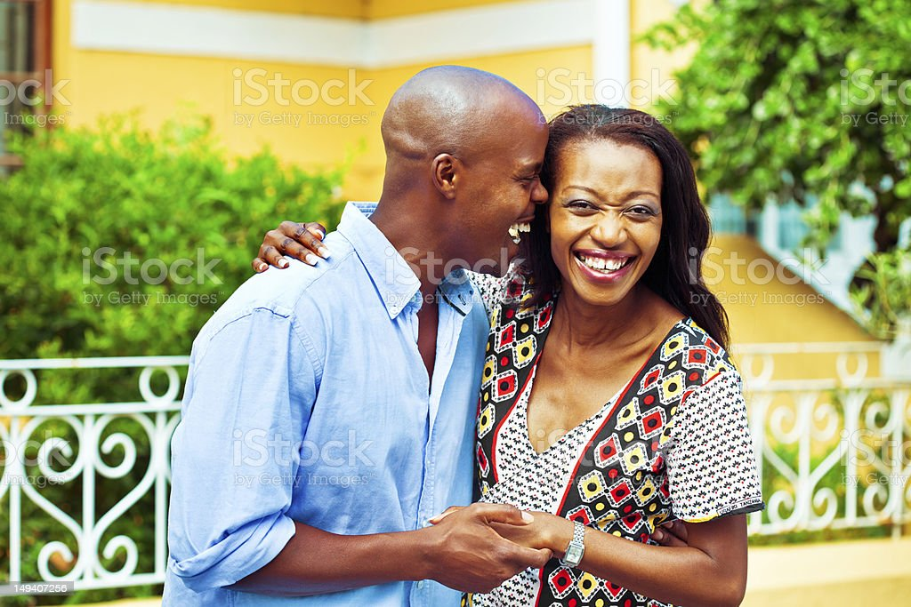Happy couple on vacation Happy african couple enjoying their summer vacation, embracing at the street. Adult Stock Photo
