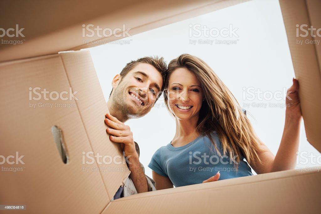 Feliz pareja que se abren, una caja - Foto de stock de 2015 libre de derechos