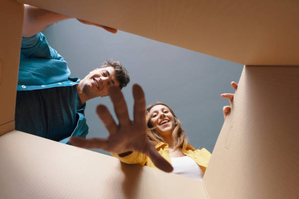 Happy couple opening a cardboard box and looking inside stock photo