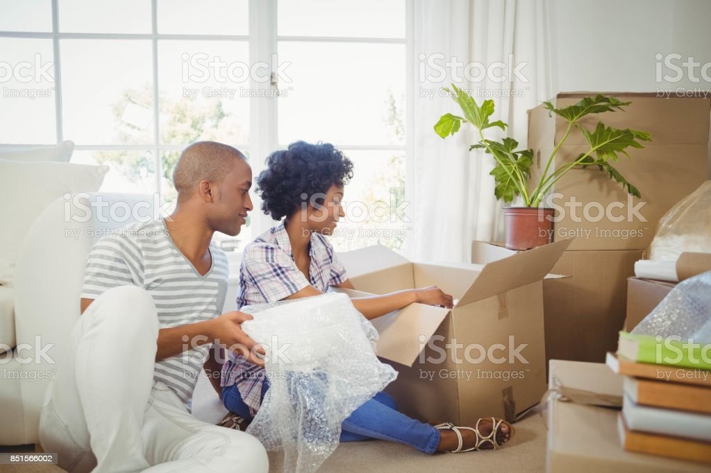 Happy couple opening boxes stock photo