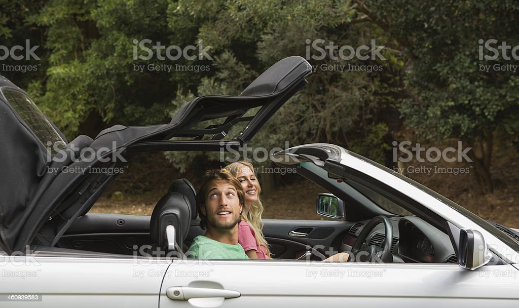 Happy couple opening the top of their convertible stock photo