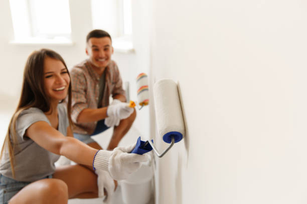 Happy Couple Painting a Wall with a Paint Roller stock photo