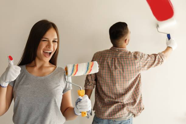 Happy couple painting wall with paint roller stock photo