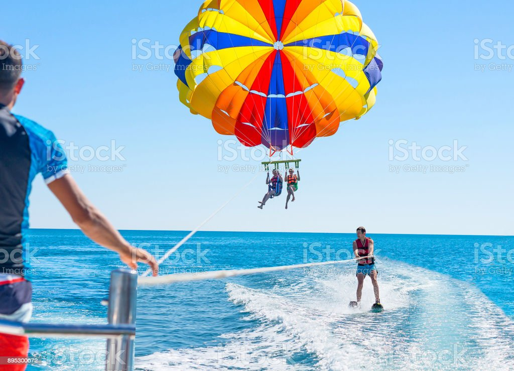 Happy couple Parasailing in Dominicana beach in summer. Couple under parachute hanging mid air. Positive human emotions, feelings, family. Young man glides on water skiing on the waves.Healthy lifestyle. stock photo