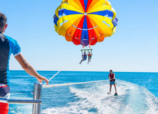 happy couple parasailing in dominicana beach in summer. couple under parachute hanging mid air. positive human emotions, feelings, family. young man glides on water skiing on the waves.healthy lifestyle. - sport wodny zdjęcia i obrazy z banku zdjęć