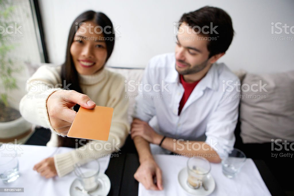 Happy couple paying for meal with card at restaurant stock photo
