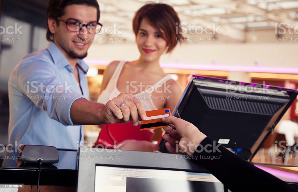 Happy couple paying movie tickets with credit card stock photo