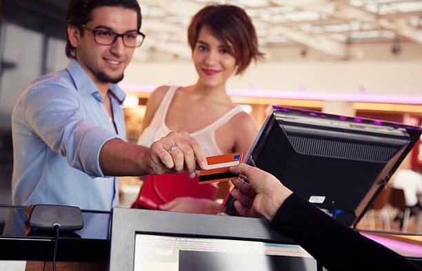 Feliz casal pagar ingressos para cinema com cartão de crédito - foto de acervo