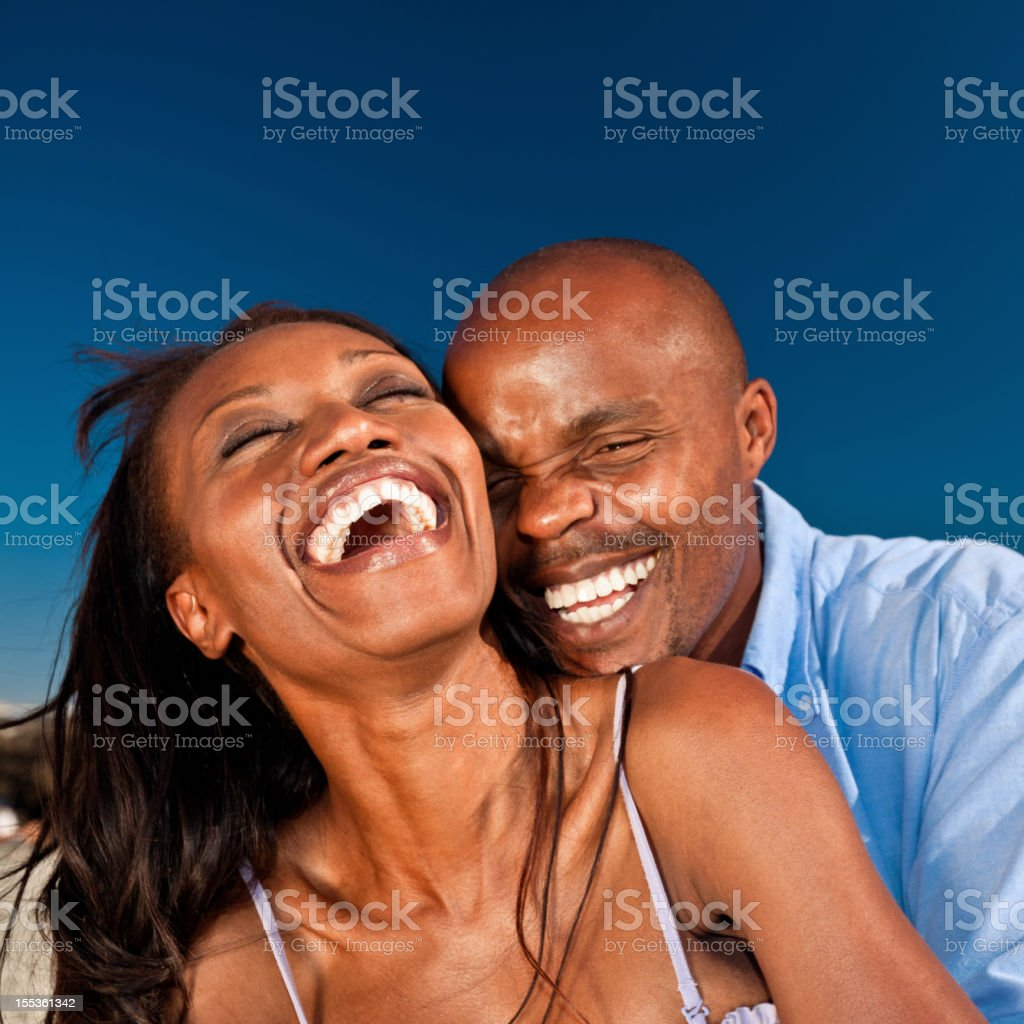 Happy couple Portrait of happy african american couple, laughing and embracing against blue sky. Adult Stock Photo