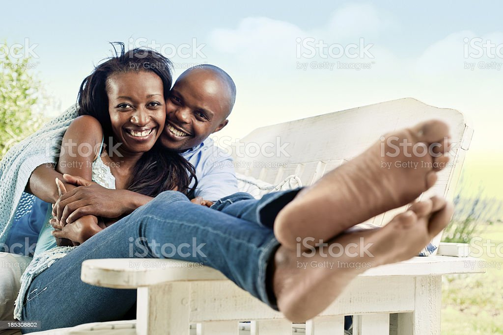 Happy couple Happy couple sitting outdoors and embracing, smiling at the camera. Adult Stock Photo