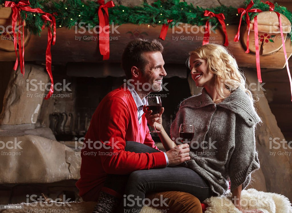 Happy couple Indoors portrait of affectionate couple flirting by fireplace at home, drinking red wine. Adult Stock Photo