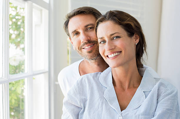 Happy couple Happy young couple sitting near window in the bedroom. Portrait of smiling man and woman looking at camera at home. Couple in pajamas during the morning. 30 34 years stock pictures, royalty-free photos & images