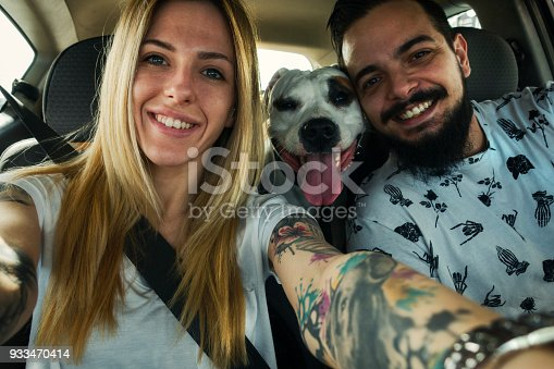 Happy couple making selfie in the car. Their dog posing with them.