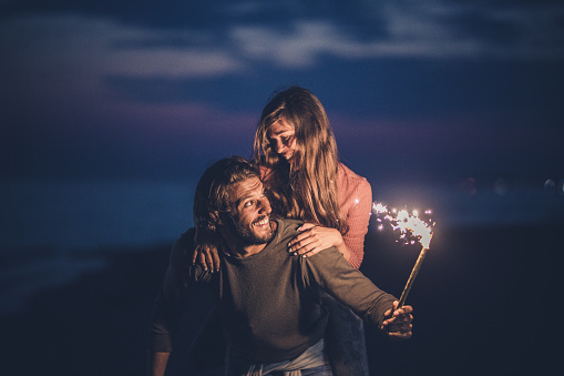 Playful couple having fun while piggybacking and holding flaming torch by night. Copy space.