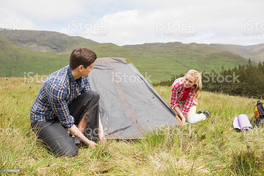 Happy couple pitching their tent stock photo