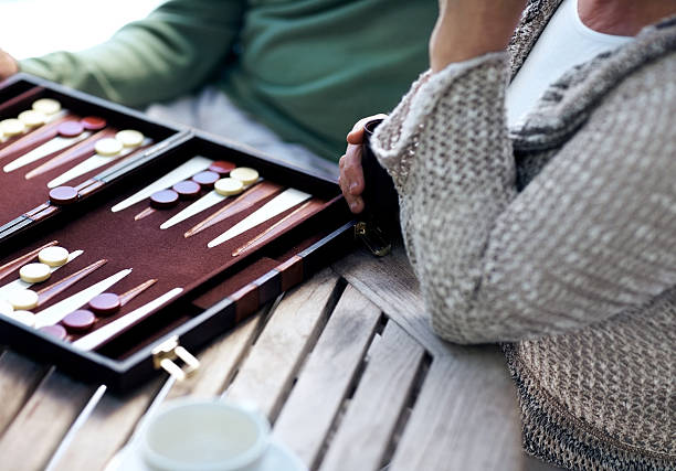happy couple playing a game of backgammon - cropped - backgammon stock pictures, royalty-free photos & images