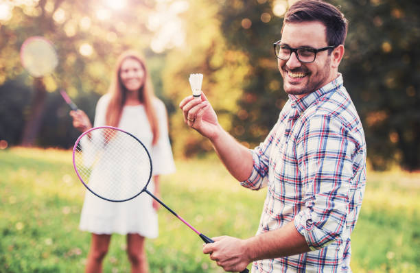 Happy couple playing badminton in the park. Sport, recreation, lifestyle, love concept stock photo