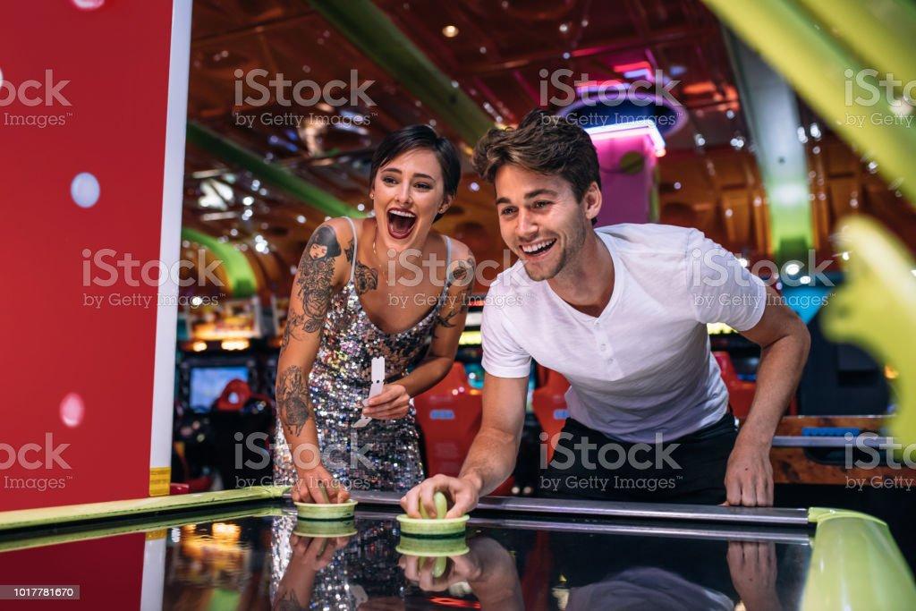 Casal feliz jogando jogo de hóquei de ar moeda operado em um salão de jogos - foto de acervo