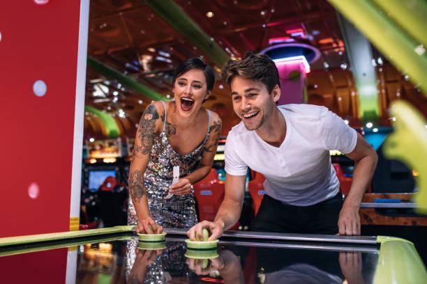 glückliches paar spielen münz-luft-hockey-spiel auf einer gaming-stube - arkade stock-fotos und bilder