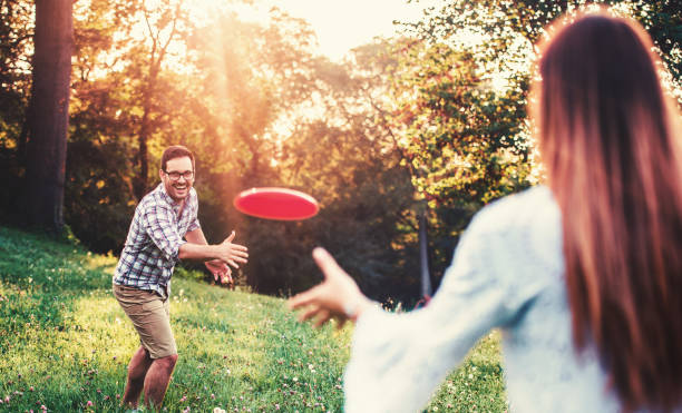 Happy couple playing frisbee in the park. Sport, recreation, lifestyle, love concept stock photo