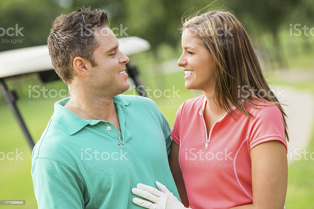 Happy couple playing golf together on course royalty-free stock photo