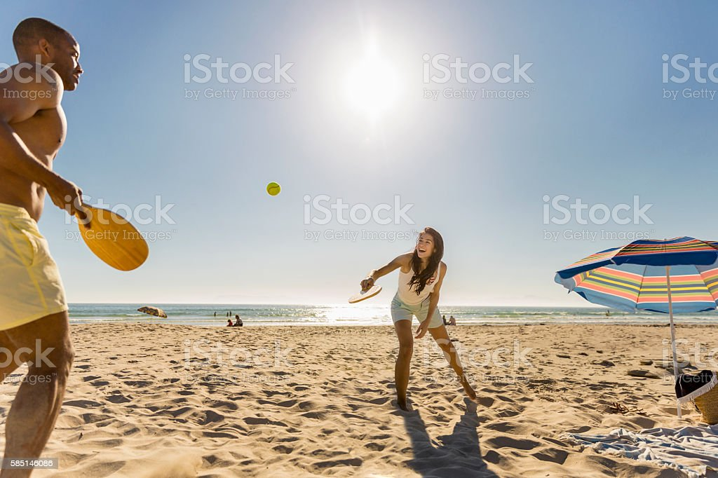 Happy couple playing tennis at beach on sunny day - foto stock