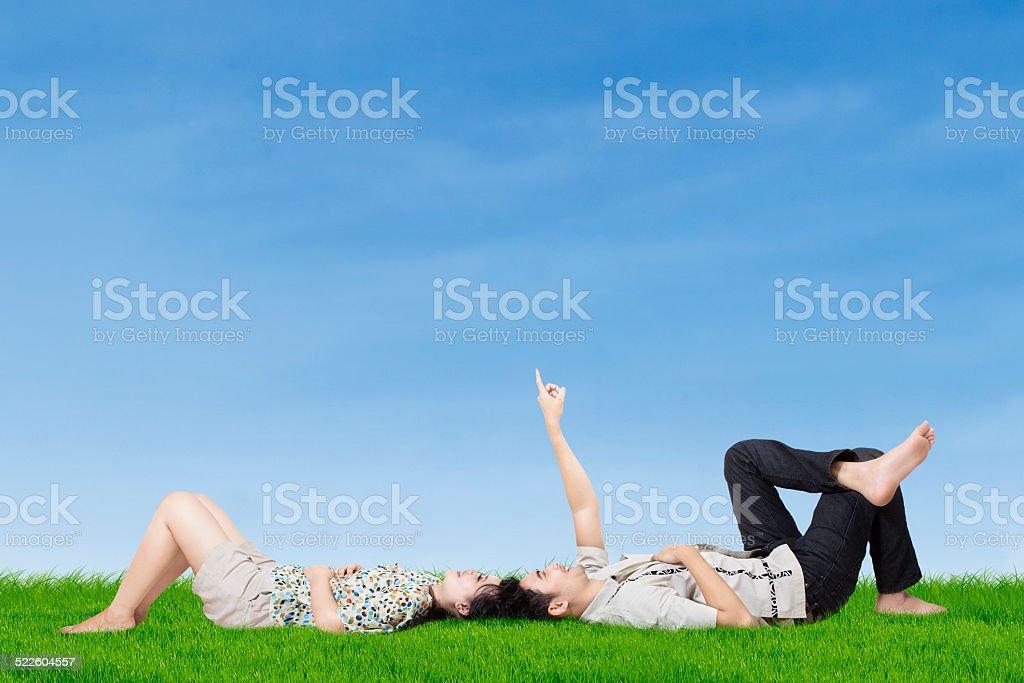 Pareja feliz apuntando en el cielo - foto de stock