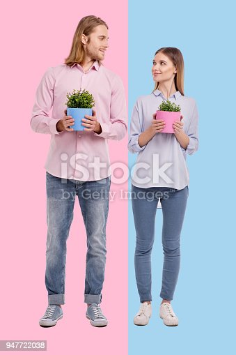 istock Happy couple posing with flower pots and exchanging loving looks 947722038