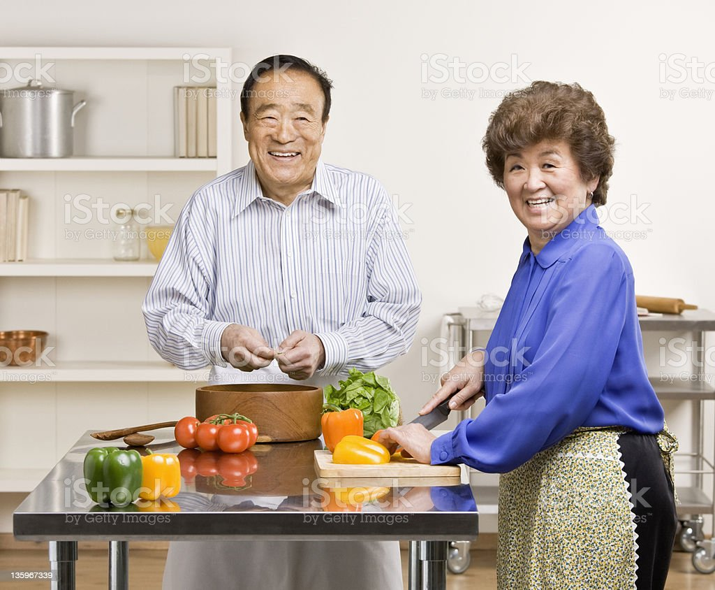 A happy couple preparing a wholesome salad for dinner royalty-free stock photo