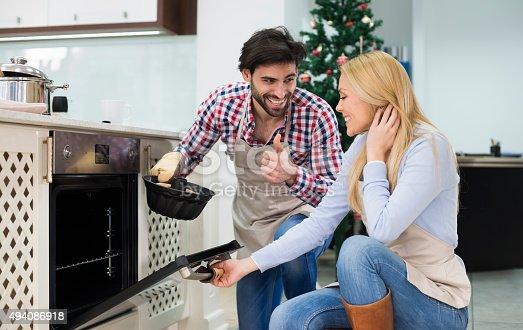 494086690istockphoto Happy couple preparing  cake for Christmas - Kugelhupf 494086918