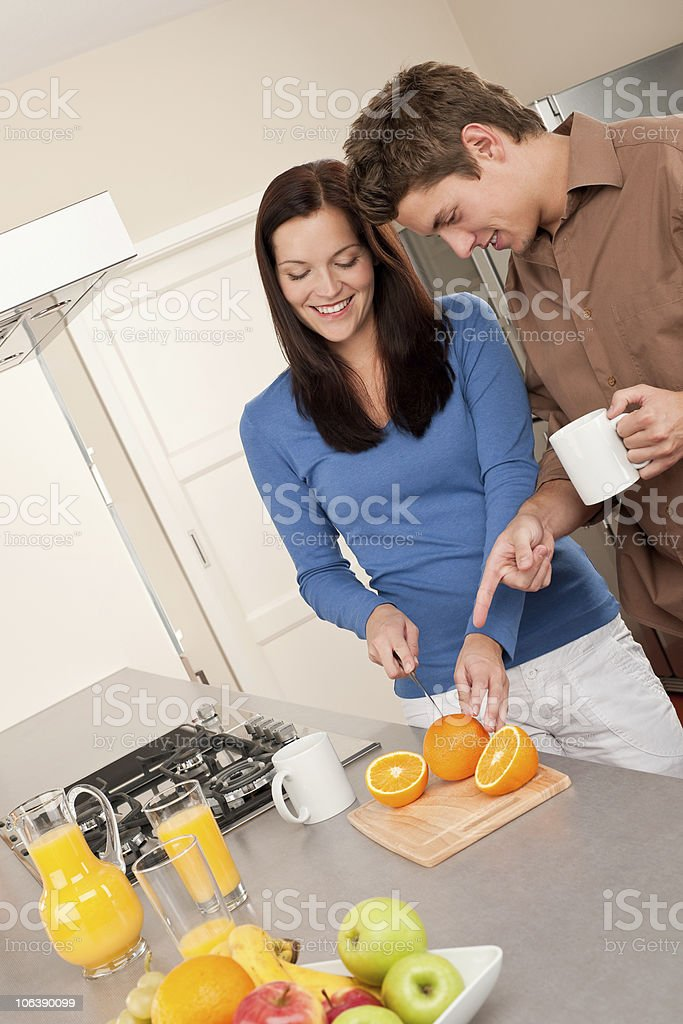 Happy couple preparing food together in the kitchen royalty-free stock photo