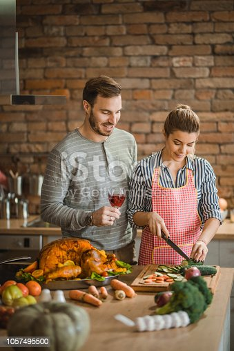 Young happy couple preparing salad for Thanksgiving meal at home.