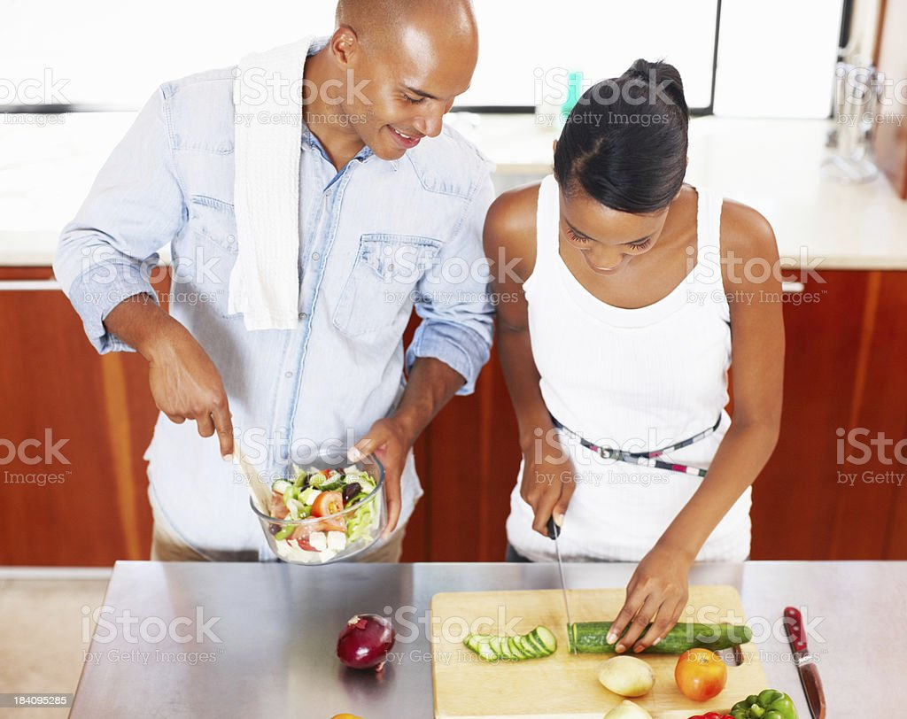 Happy couple preparing salad in kitchen royalty-free stock photo