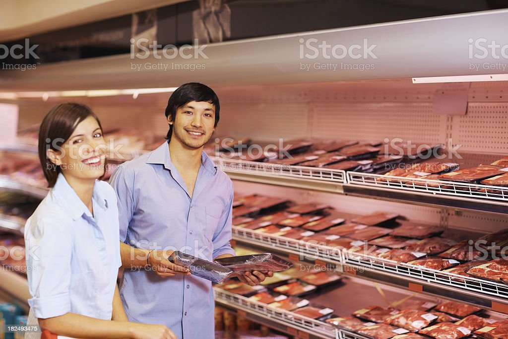 Happy couple purchasing a packet of meat at the supermarket royalty-free stock photo