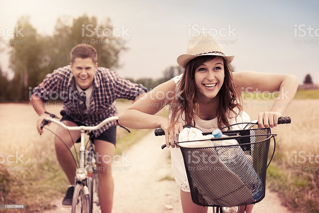 Happy couple racing on bikes stock photo