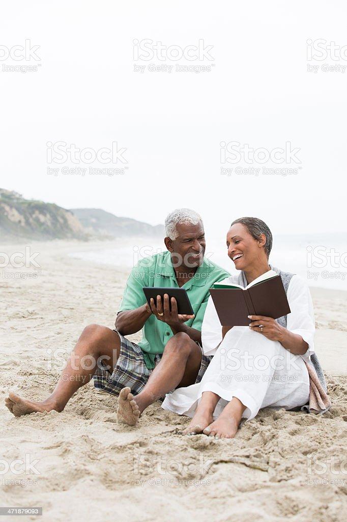 Happy couple reading at the beach royalty-free stock photo
