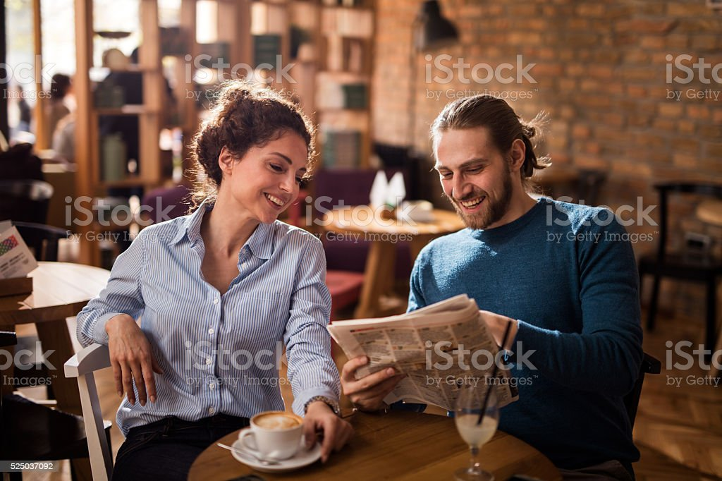 Happy couple reading newspaper in a cafe. stock photo