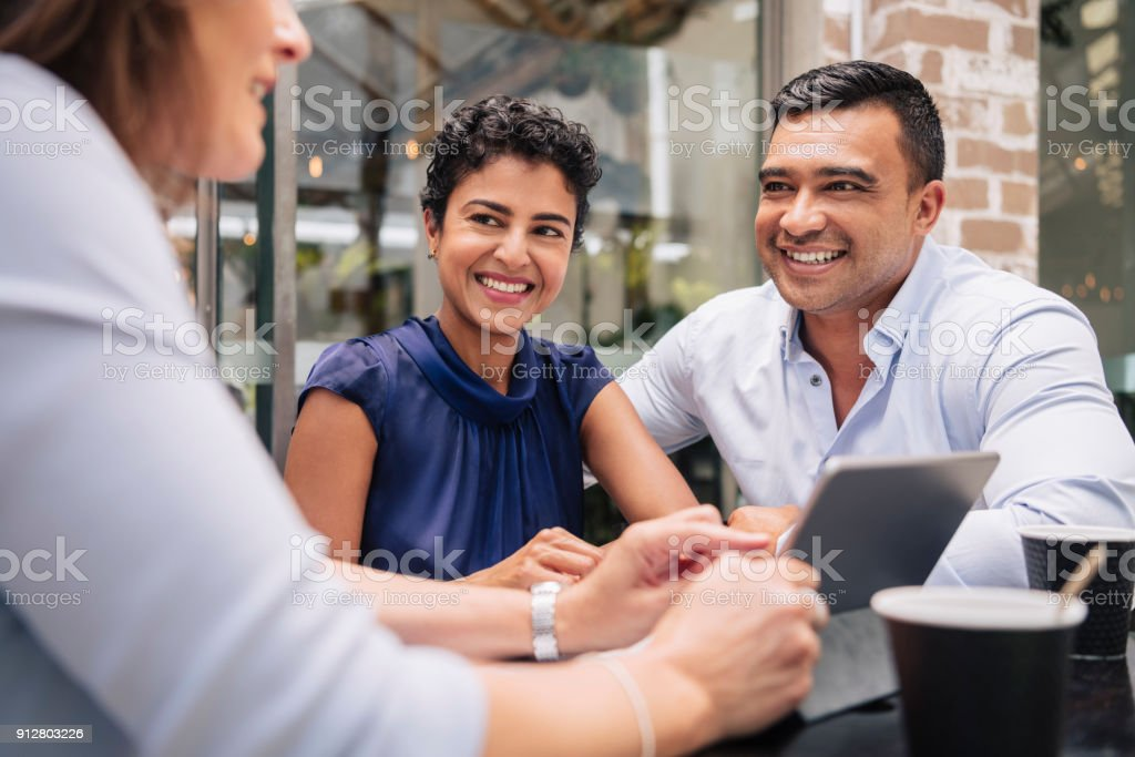 Happy couple receive good news from professional businesswoman stock photo