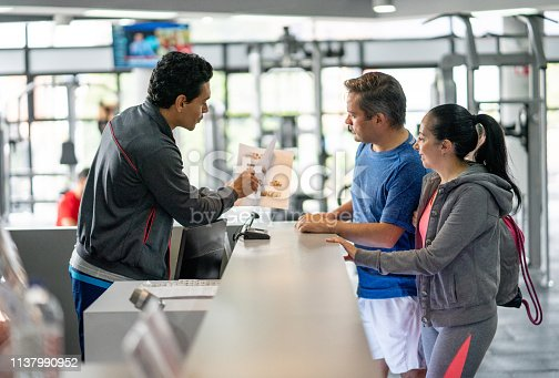 Happy couple registering at the gym while employee explains benefits showing them a catalogue - healthy lifestyles