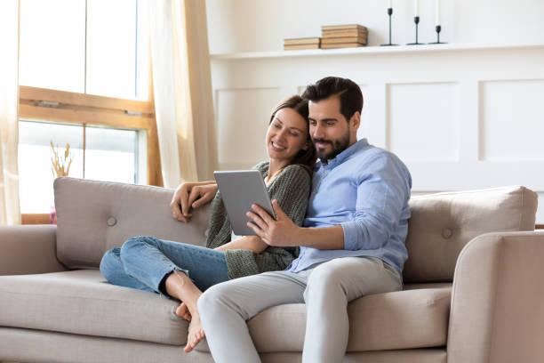 幸せなカップルは一緒にタブレットを使用してソファでリラックス - 両親 ストックフォトと画像