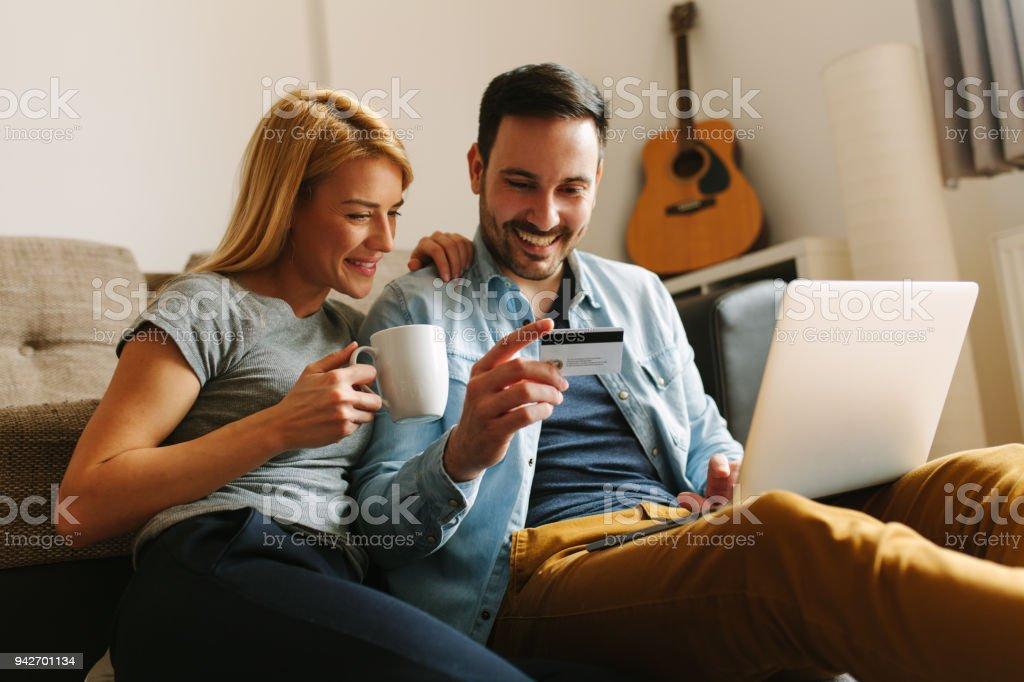 4d33148c38 Casal feliz relaxado em casa, fazendo compras on-line foto de stock royalty-