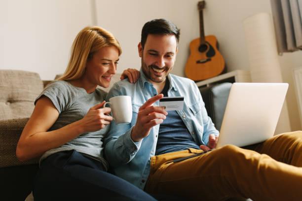 glückliches paar entspannt zu hause tun, einige online-shopping - sofa online kaufen stock-fotos und bilder
