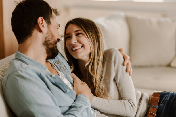 gelukkig paar ontspannen thuis en kijken naar elkaar - verliefd worden stockfoto's en -beelden