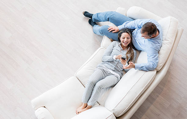 Happy couple relaxing at home Happy couple relaxing at home using app on a smart phone - relationship concepts model home stock pictures, royalty-free photos & images