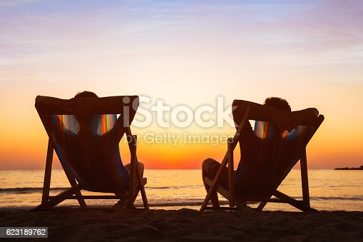 istock happy couple relaxing in beach hotel  at sunset, honeymoon 623189762